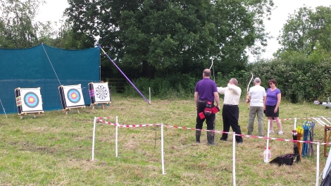 People trying archery with coaches