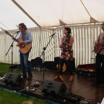 Folk group trio performing in a marquee