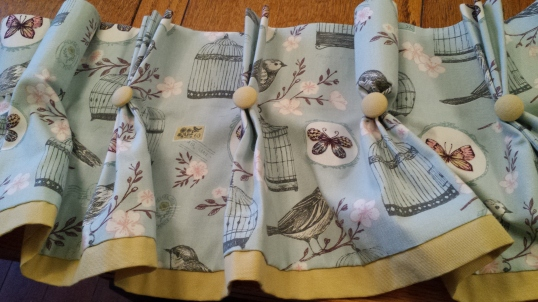 Blue patterned valance with yellow trim and buttons