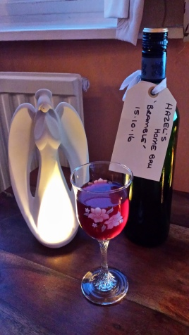 Bottle of homemade red wine, a full glass and an angel tealight holder