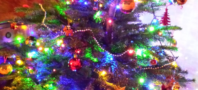 Christmas tree with bright coloured lights and gifts underneath