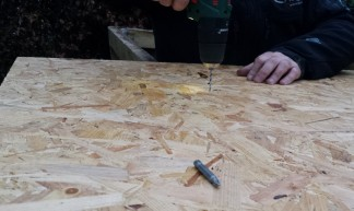 OSB boards being screwed down with a drill