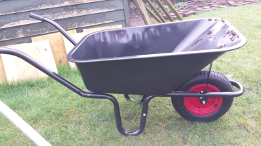 Black wheelbarrow with a red wheel