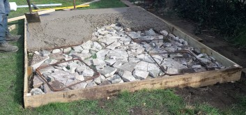 Part concreted base with broken stones under the concrete