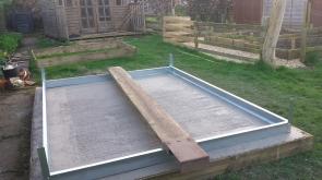 Concrete greenhouse base on a lawn