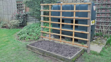Raised bed with trellis in front of green oil tank