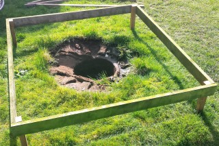 Wooden frame on a lawn surrounding a hole in the ground