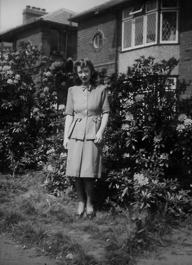 Black and white photo of a young woman in front of a house in the 1950s
