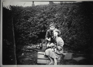 Woman sitting on a box in a garden with a black dog and a boy