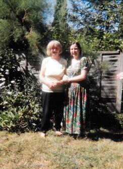 Older woman and young woman arm in arm in a garden