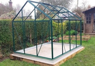 Greenhouse frame with no glass on a concrete base in a garden