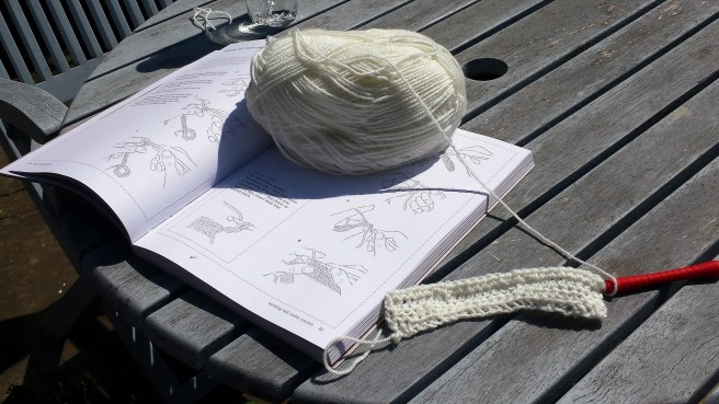 Piece of white crochet on a red hook, with a ball of wool sitting on an instruction book