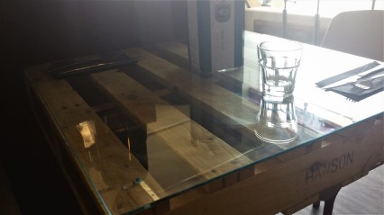 Cafe table made from a wooden pallet covered in glass