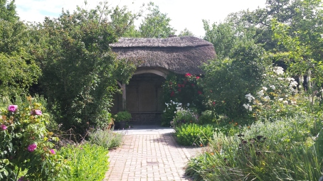 Small thatched building in a cottage garden setting