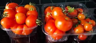 2 clear plastic containers holding large and small tomatoes and several strawberries
