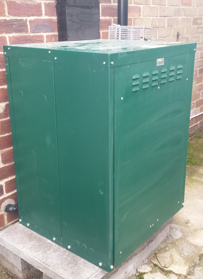 Green external boiler cupboard next to a red brick house wall
