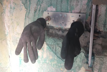 Black gloves hanging from a metal plate on a wall with no plaster