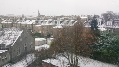 A dusting of snow on grey granite buildings