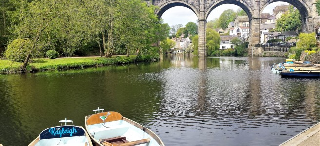 River with a viaduct in the background and rowing boats in the foreground