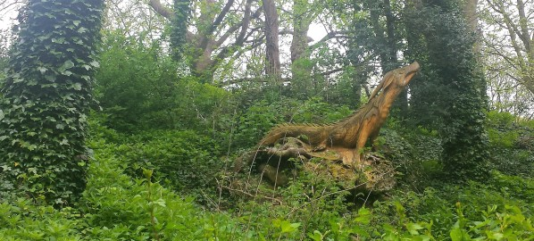 Wooden sculpture of a lizardlike creature sitting in a woodland setting