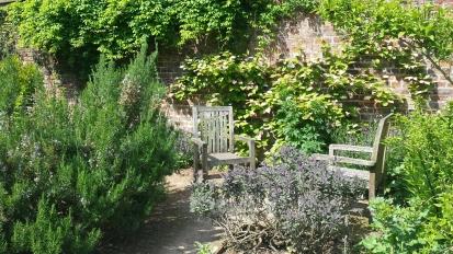 2 chairs set into deep garden borders in a walled garden