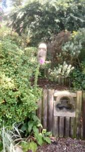Stone head placed amongst planting with small gate in foreground