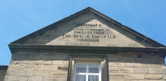 Pitched stone roof with carved inscription