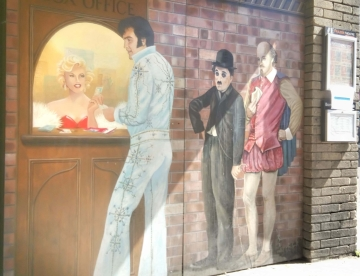 Outdoor mural of box office window with Marilyn Monroe selling tickets and Elvis, Charlie Chaplin and Shakespeare queuing to buy