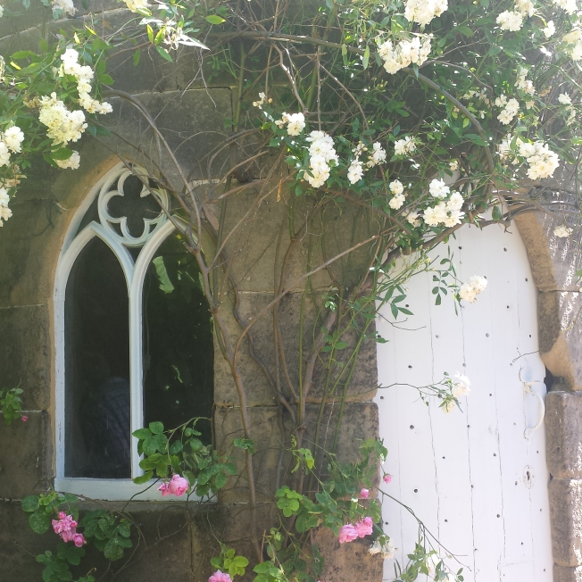 Round stone tower with Gothic arched window and roses around the door