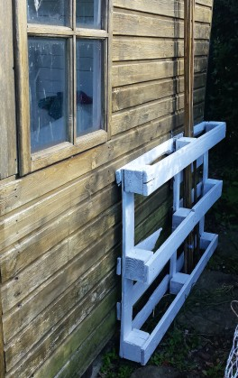 White painted pallet screwed vertically to wooden wall of summer house