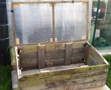 Open empty cold frame made from pallet wood with a plastic sheet lifted lid