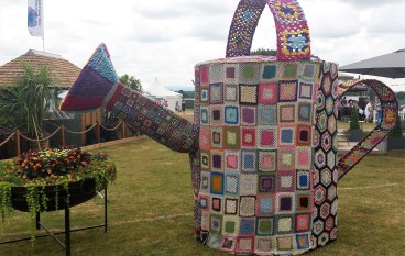 Giant watering can covered in multicoloured crocheted squares