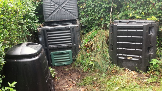 3 black plastic compost bins in the garden