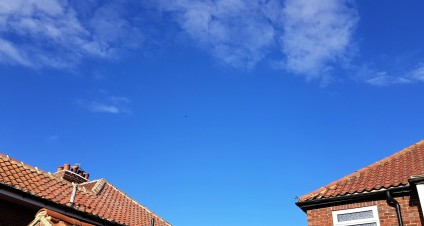 Bright blue sky with wispy white clouds drifting across it