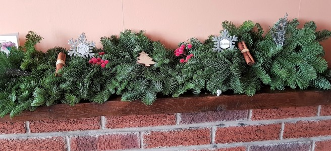 A green pine garland on a wooden mantlepiece above a red brick fireplace
