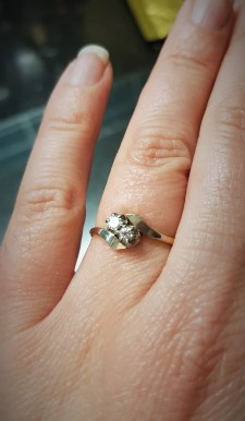Hand wearing a 2-stone diamond engagement ring