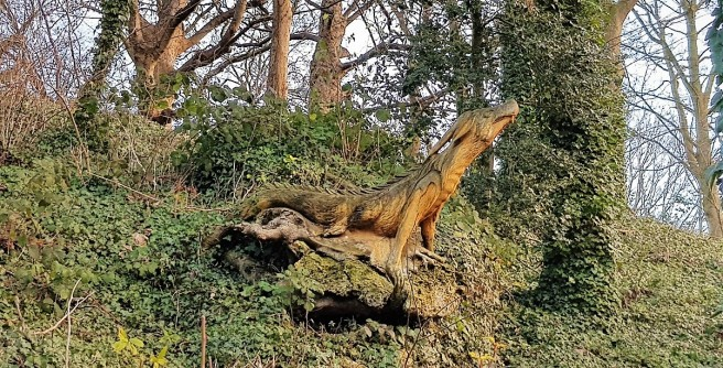 Wooden dragon sitting in a woodland setting