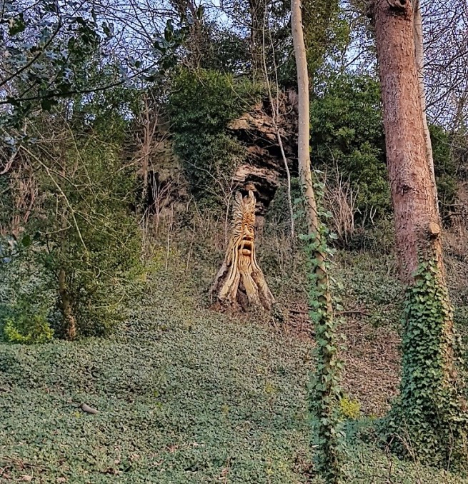 Green man carved into a tree trunk in a woodland