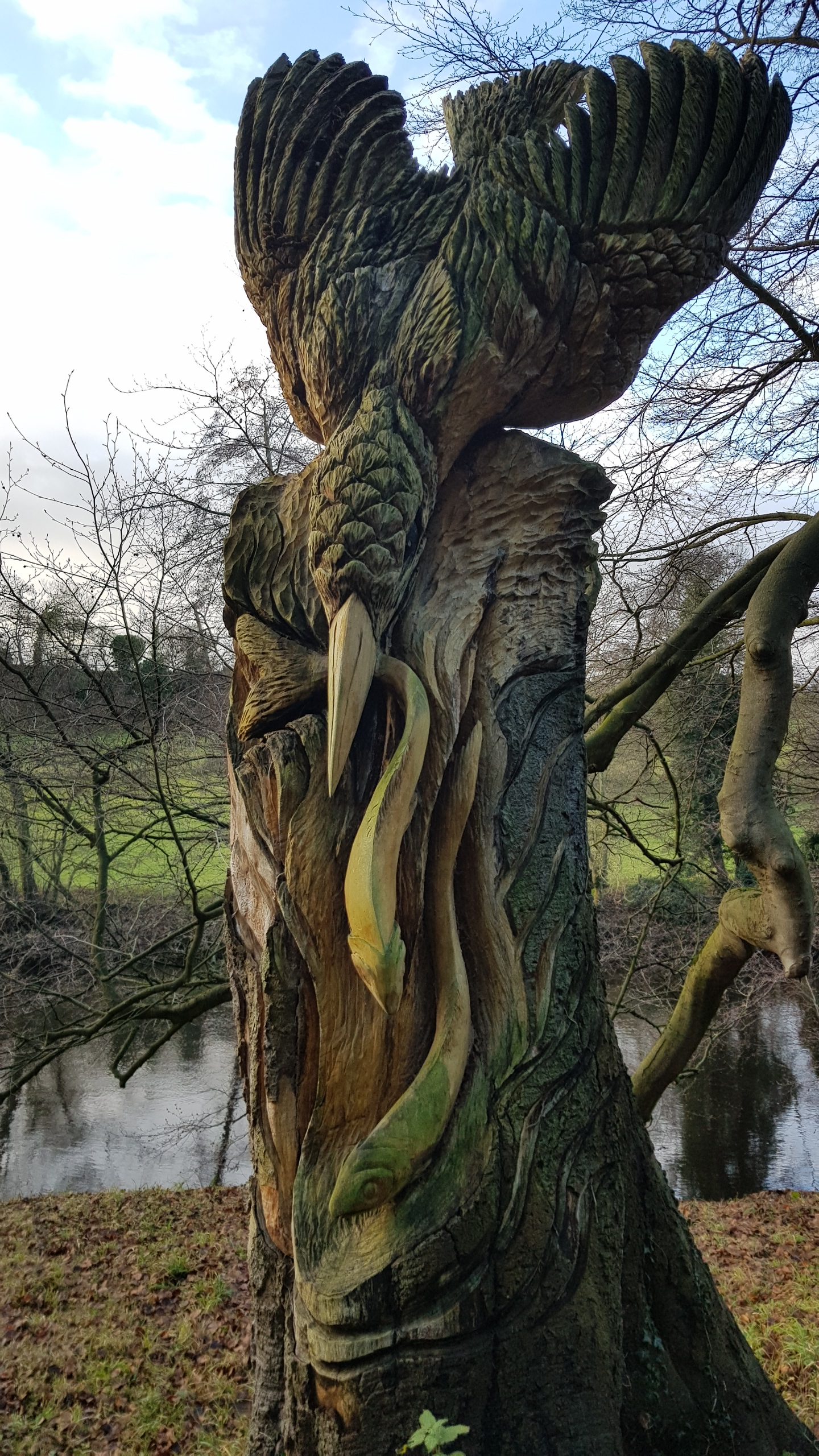 Wooden kingfisher catching fish carved into a tall stump of a tree trunk