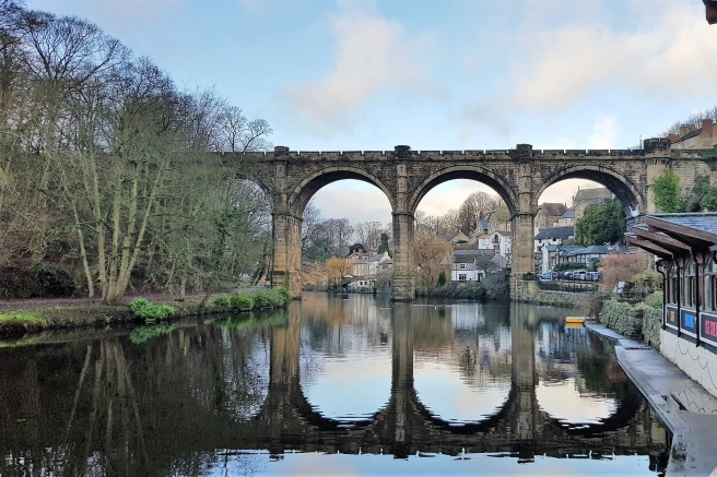 Viaduct over a river with bridge and sky reflected in the water