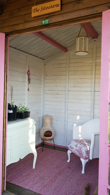Summer house interior with painted white wooden walls and pink beams and doorframe