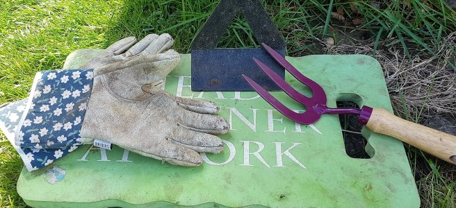Green garden kneeler with a hoe, a handfork and a pair of leather gardening gloves