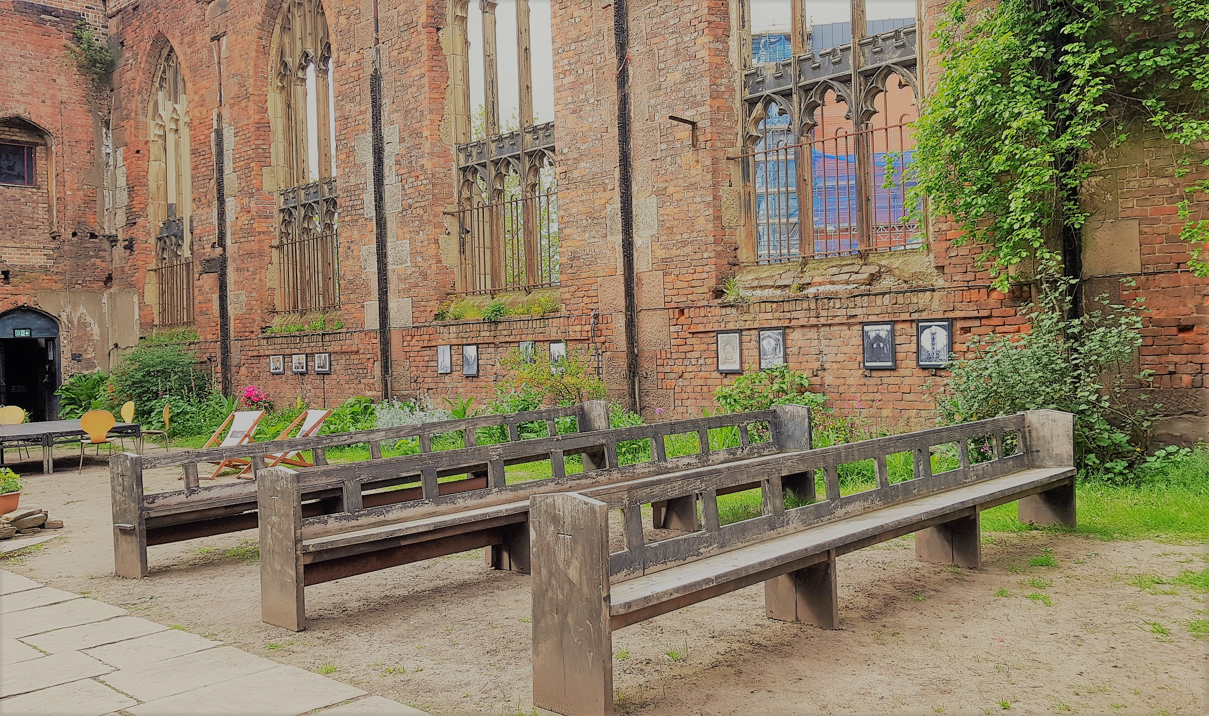 3 wooden pews in a church shell open to the weather