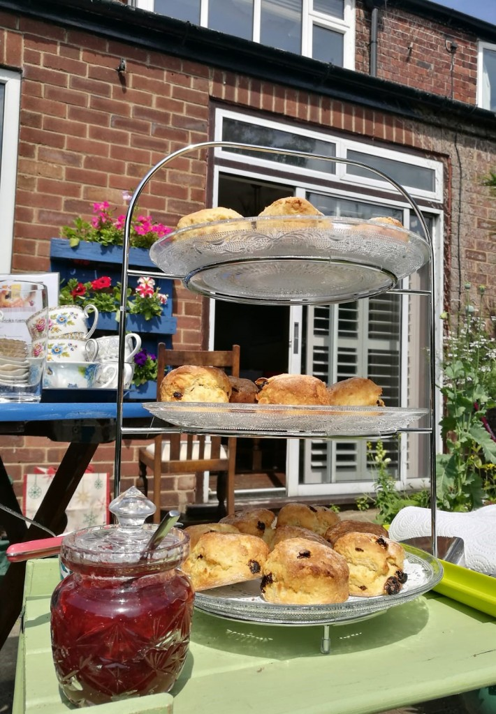 3 tiered cake stand holding scones with a glass jam pot at the side and china teacups behind