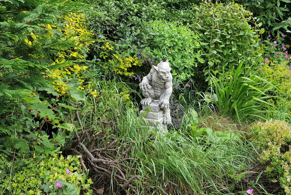 Stone gargoyle sitting amongst lots of green foliage