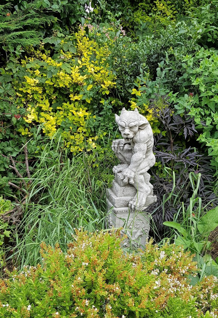 Stone gargoyle amongst lots of green foliage